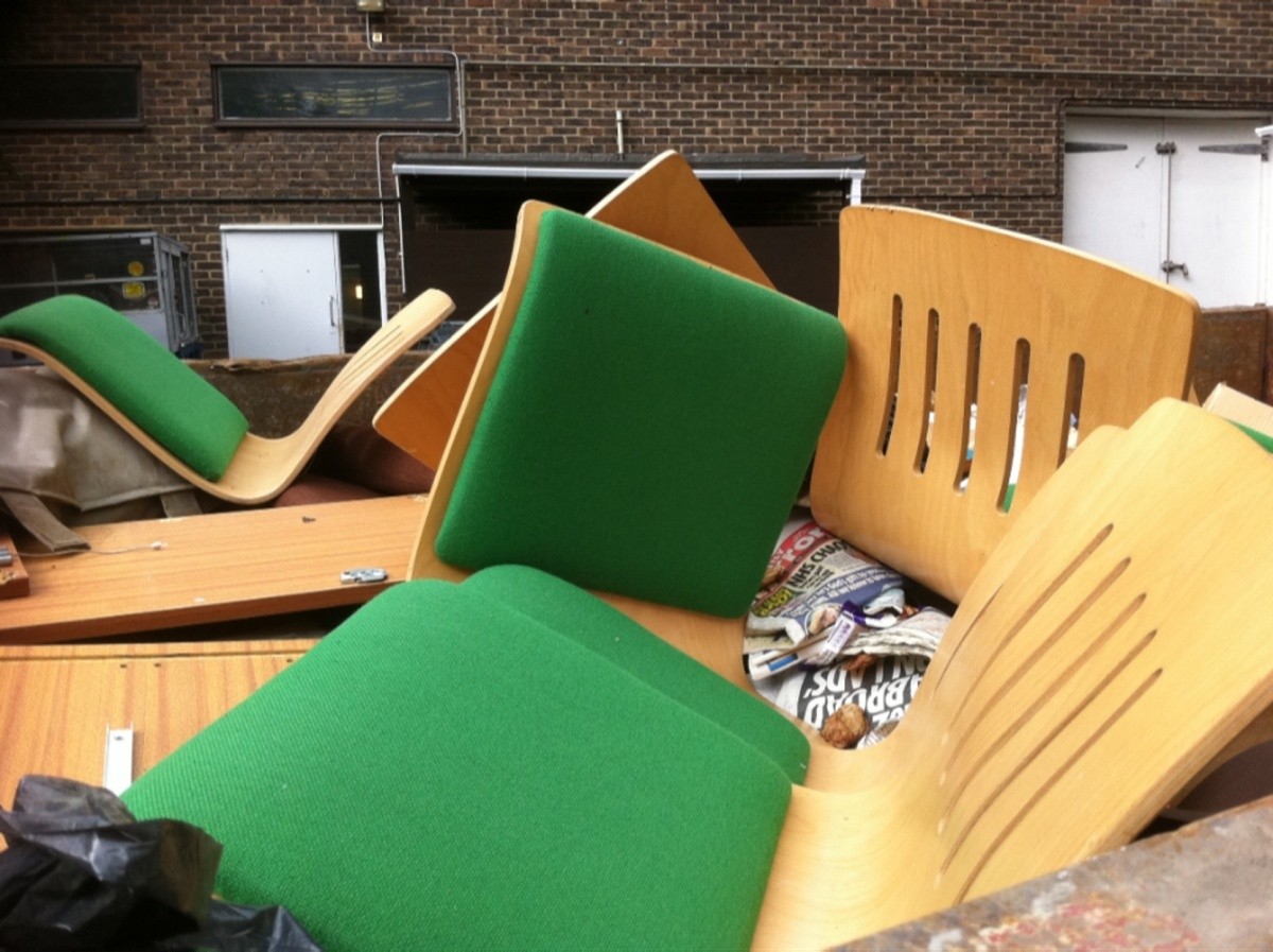 chairs in a skip dumpster