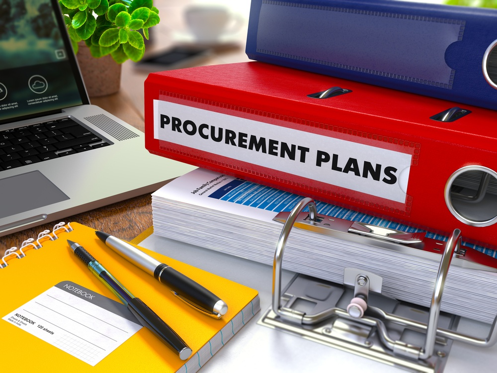 Red Ring Binder with Inscription Procurement Plans on Background of Working Table with Office Supplies, Laptop, Reports. Toned Illustration. Business Concept on Blurred Background..jpeg