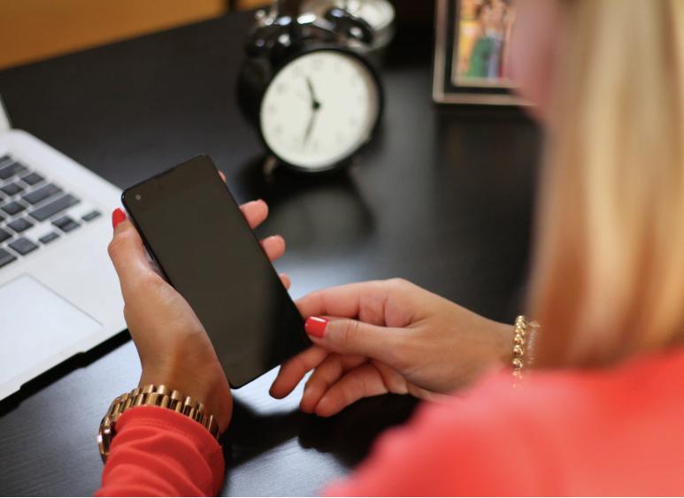 woman sitting holding smartphone near laptop photo – Free Clock Image on Unsplash