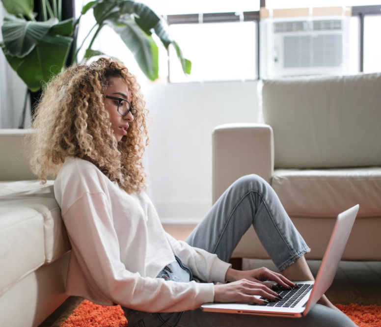 woman sitting on floor and leaning on couch using laptop photo